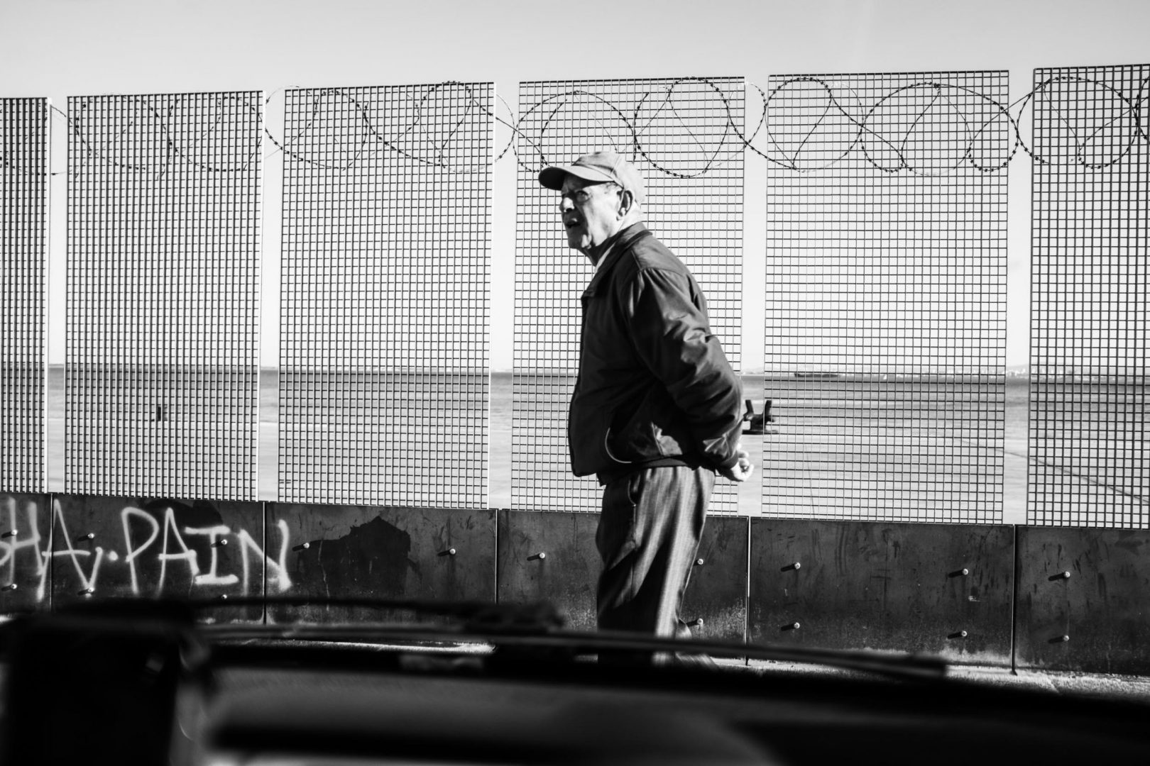I was sitting in the car with my friend and suddenly this man passes right in front of us. The graphic lines of the fence, his expression, the framing through the car window, all made for a nice frame.